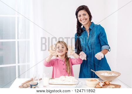 Sweet time of family cooking. Mother and daughter having fun while preparing meal. Nice white interior. Mother and daughter having hands smeared with dough
