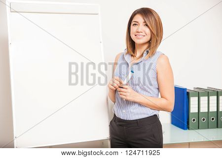 Beautiful female tutor standing next to a flip chart and about to teach a class