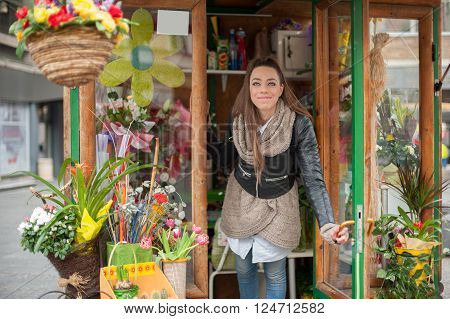 Beautiful young woman in the street flower shop