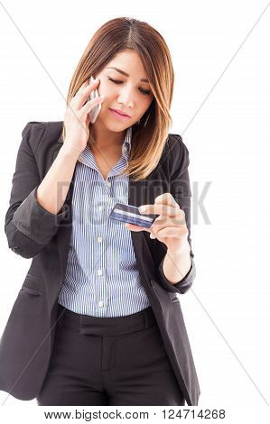 Good looking young woman in a suit calling customer service at her bank to activate her new credit card