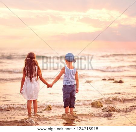 Girl and boy watching sunset on the beach.