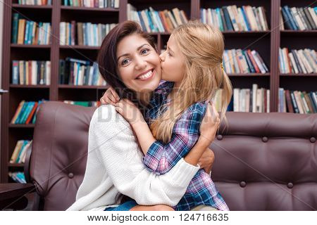 Photo of mother and little daughter. Nice cozy interior with big bookcase. Mother looking at camera and smiling while daughter kissing her