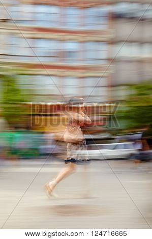 Blurred motion image of a woman walking down a city street