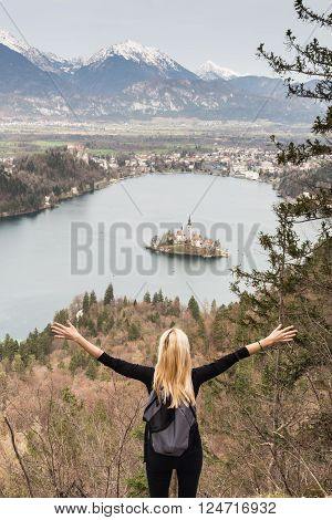 Made it. Young spoty active lady with hands rised admiring beautiful nature around Bled Lake in Julian Alps, Slovenia.