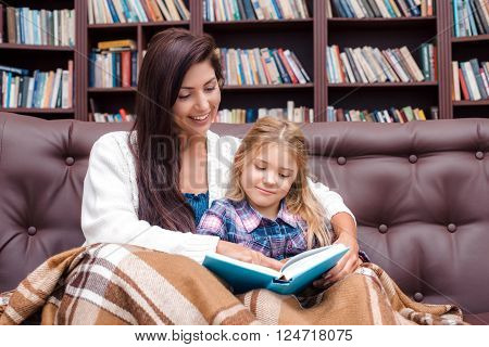 Photo of mother and little daughter. Nice cozy interior with big bookcase. Mother and daughter reading bedtime story