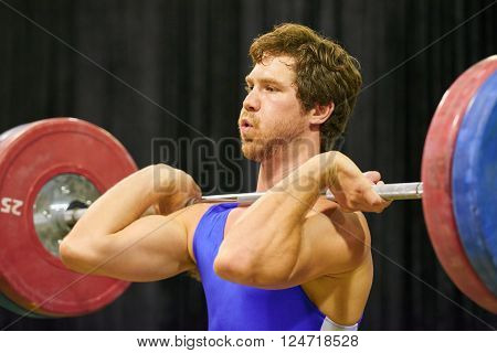 A weight lifter lifting weights during a competition