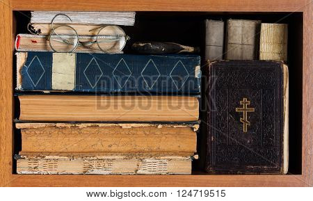 Library book shelf with Holy Bible book, aged books covers, spectacles. Vintage wooden frame. Christianity conceptual image.