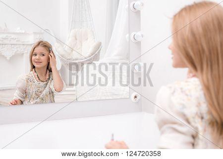 Little beautiful girl applying makeup in front of mirror. Nice cozy white bedroom