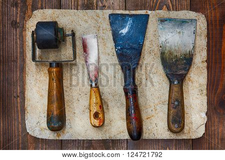 Retro design tools for artist workshop: rubber roller, different size putty knives on stone plate and wooden background. Techical service diy tools, decorator accessories concept. soft focus