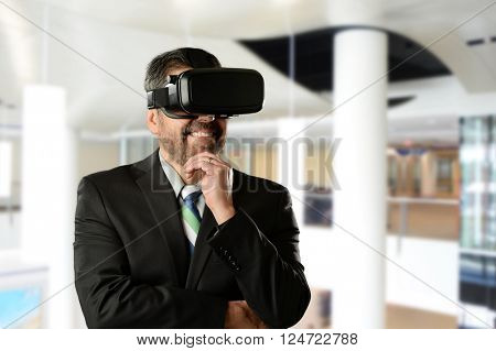 Mature Businessman wearing Virtual Reality Goggles inside an office building