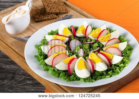 Delicious Spring onion eggs radish salad in a white dish with fork on a cutting board with wholegrain crispbread on an old rustic wooden table horizontal close-up top view