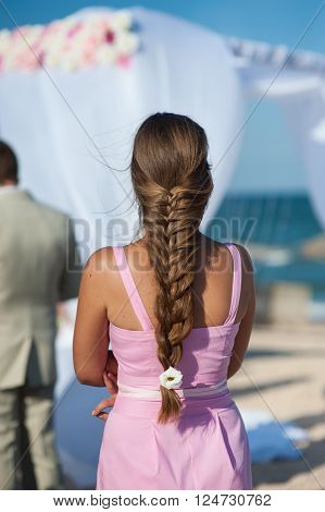 woman with a long braid at the wedding ceremony on beach.