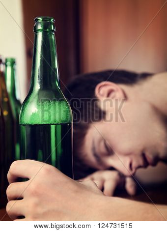 Toned Photo of Young Man sleep with the Beer on the Table