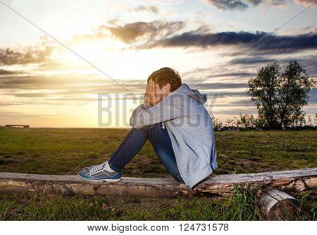 Sad Teenager sit on the Log on the Sunset Background