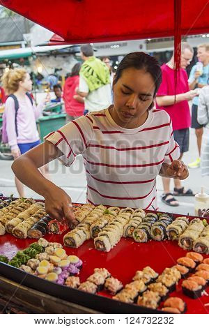 KO PHA NGAN, THAILAND - FEBRUARY 7, 2016: Unidentified woman selling food on the street. Street food is a quintessential part of the Thai experience.