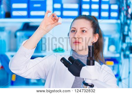 woman  technician with microscope slide in lab, toned background