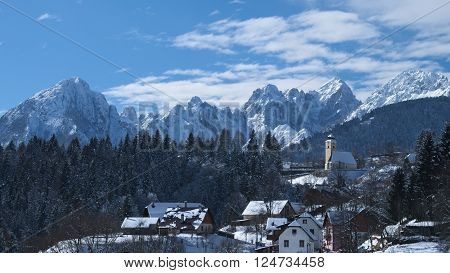 Winter view of the church of Coccau with snow and the Julian Alps in the background