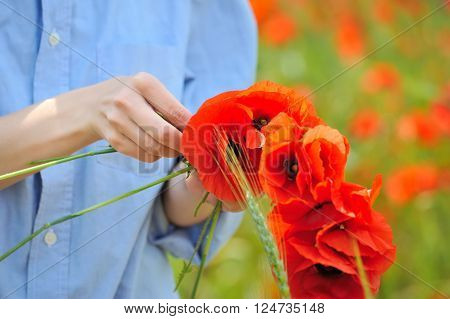 Her hands weave of flowers wreath. On the field