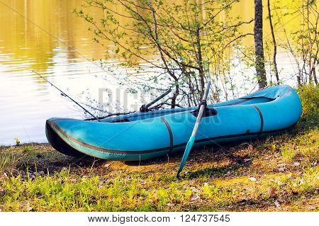 small rubber boat on the lake shore