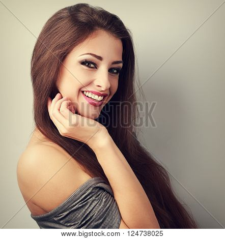 Beautiful laughing brunette woman with happy smile on with empty copy space. Toned closeup portrait