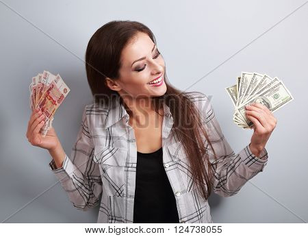 Happy business woman thinking that currency to choose dollars or rubles and choosing dollars holding money in different hands.