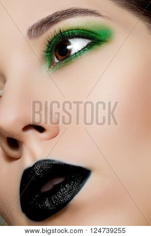 Beauty portrait of a girl model with make-up black lips and green eyes. Creative Professional makeup: black lipstick and green eye shadow.