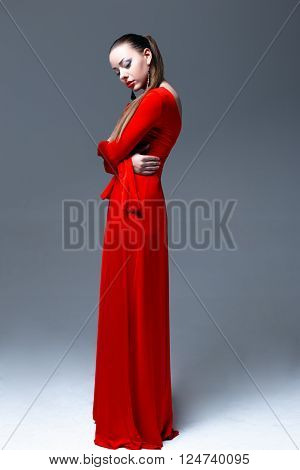Fashion shoot of beautiful woman in a long red dress. Glamour girl with bright makeup. Beauty female. Perfect skin and make up. Red lips. Beautiful young brunette woman with trendy accessories posing in studio.