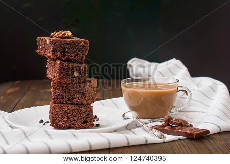 slices of homemade chocolate brownie with walnuts stacked pyramid and a glass of milk for breakfast low key selective focus
