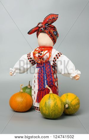 Doll in Ukrainian costume inspired by traditional Slavic rag dolls with ornamental gourds around