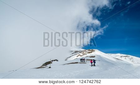 Winter landscape in the mountains. Group of hikers. Mountain ridges covered by snow in winter in Europe.