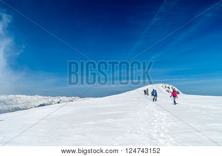 Winter landscape in the mountains. Group of hikers. Mountain ridges covered by snow in winter in Europe. ** Note: Soft Focus at 100%, best at smaller sizes