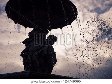 A silhouette of a  fountain in rossio square lisbon