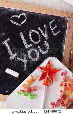 I love you, written on a blackboard with chalk, caramel, candy, star, wand, valentines day, valentine, romantic declaration, sweet tooth, a space for inscription