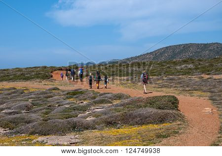 Cyprus. Akamas. Mediterranean Sea. November 24, 2015. A group of tourists with large backpacks are on the sandy road to the sea