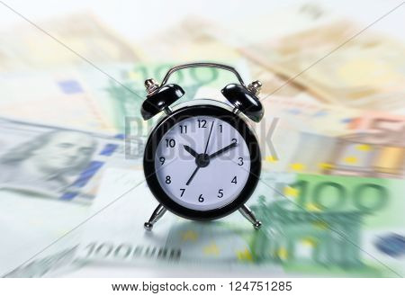 Time is money concept. Blurred on purpose with focus on the clock for a flow sensation