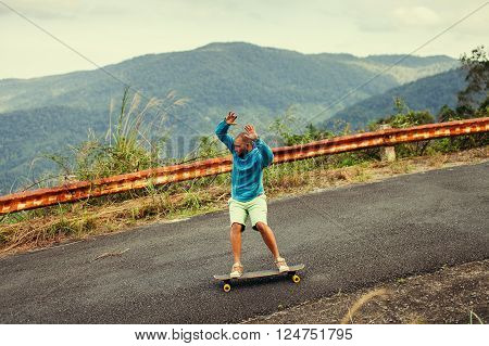 Hipster man longboarding extreme action on highway in Asia.
