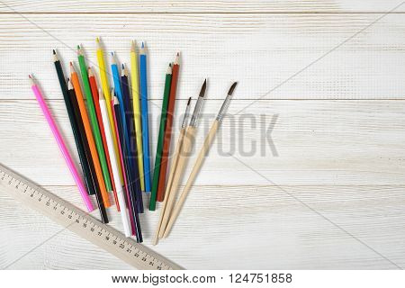 Layout of set of colorful sharp pencils, a centimeter rule and paint brushes on a wooden blank board. Art composition.