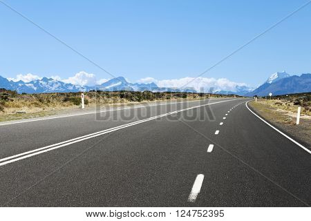 empty asphalt road near snow mountains in new zealand