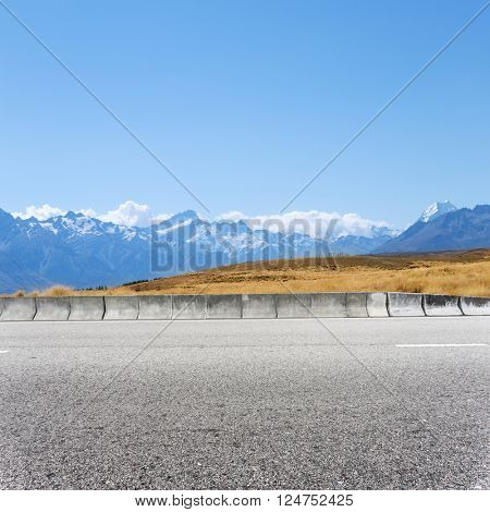 empty concrete road near snow mountains in new zealand