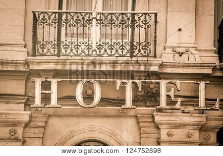 Hotel sign with a balcony above it