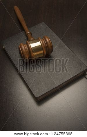 Judicial wooden gavel on a black book