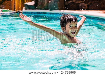 Young boy kid child eight years old splashing in swimming pool having fun leisure activity open arms