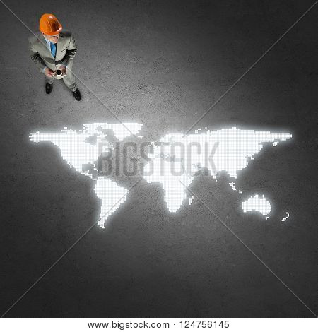 Top view of thoughtful engineer man looking at glowing world map on concrete floor