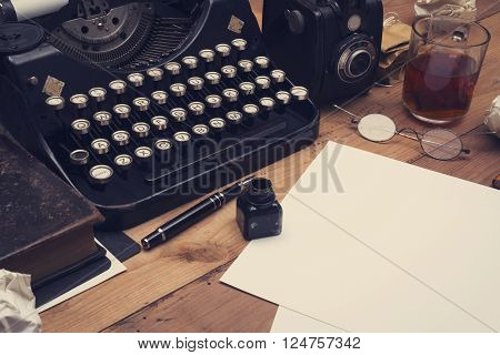 Retro office desk with old typewriter, camera and stationary