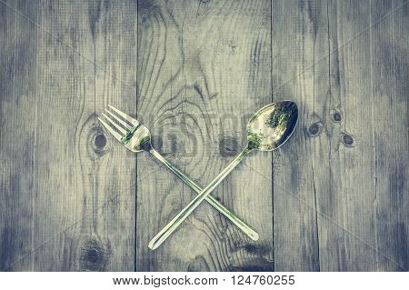 Vintage wood background with silver cutlery. Rustic wooden table and crossed silvery cutlery. Can be used as background menu for restaurant with Mediterranean and Caribbean cuisine