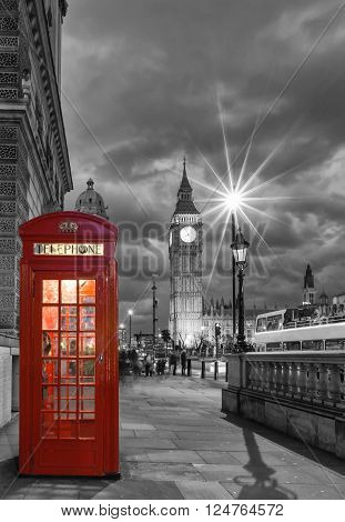 Red telephone booth in front of the Big Ben in London, United Kingdom, by night