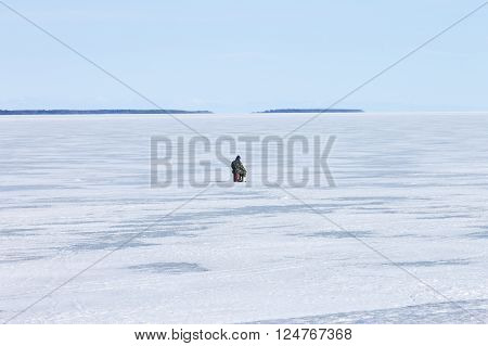 lonely fisherman on the frozen lake on a clear winter day fishing Ice hole
