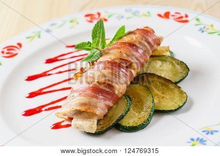 chicken roll wrapped in strips of bacon