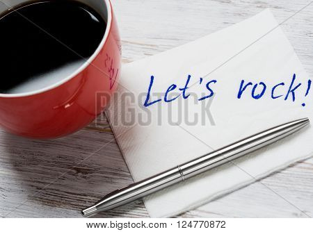 Cup of coffee and napkin with writings on table
