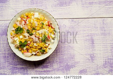 crab salad in a plate on a wooden table.Rustic style.Top view. Free space for text.